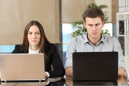 61935133 - front view of two angry businesspeople using computers disputing at workplace and looking sideways each other with envy